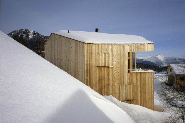 A wooden house in the snow, construction of houses of wood. A big piece of wood carved to set this house in the mountain.